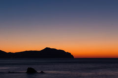 Rocks, sea and sunrise. A view of a promontory during the sunrise Stock Images