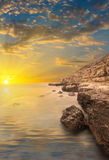 Rocks, sea, sunset with rays. Stock Images