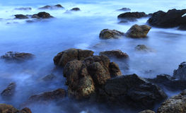 Rocks in the sea wave at dawn moment Stock Image
