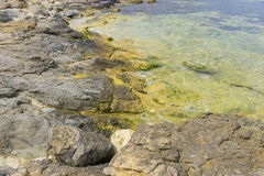 Rocks by the sea with waves of the Mediterranean sea next to the Stock Photo