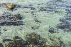 Rocks by the sea with waves of the Mediterranean sea next to the Royalty Free Stock Images
