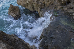 Rocks by the sea with waves of the Mediterranean sea next to the Stock Photography