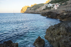 Rocks by the sea with waves of the Mediterranean sea next to the Royalty Free Stock Photos