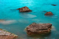 Rocks in blue water Stock Photos