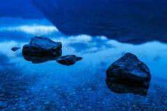 Rocks in shallow lake water at night Stock Image