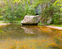 Rocks in a shallow river Stock Images