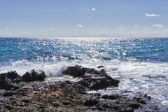 Rocks, shiny sea and blue sky Stock Image