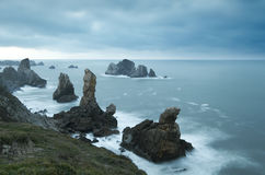 Rocks on the shore at sunset with cloudy sky. Cantabria Stock Photography