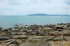 Rocks on shoreline with sea and mountain background Royalty Free Stock Photography
