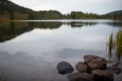 Rocks on the shoreline of a tranquil lake Stock Photography