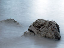 Rocks in silky smooth water with copyspace Stock Images