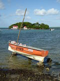 Small boat careened on rocks  Stock Photos
