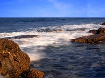 Rocks and Smooth Ocean Waves Royalty Free Stock Images