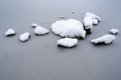 Rocks with snow. Snow covered rocks in frozen lake Royalty Free Stock Photos