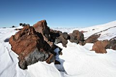 Rocks in snow against a clear blue sky near Elbrus Royalty Free Stock Image