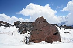 Rocks in snow against a clear blue sky near Elbrus Royalty Free Stock Photography