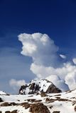 Rocks in snow and blue sky with clouds Royalty Free Stock Image