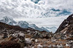 Rocks and snow peaks in Nepal Himalayas. Himalayan scenery in Nepal near Gokyo, with textured cloudy sky and high snow covered peaks close by stock photography
