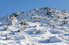 Rocks and snow in wintry mountain. Snow covered rocks in wintry mountain with blue clear sky Stock Photo