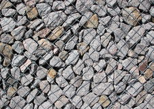 Rocks in  solid metal grid construction diagonal Royalty Free Stock Photography