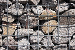 Rocks in solid metal grid wall closeup Royalty Free Stock Images