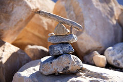Rocks are stacked in a pyramid shape with a piece of driftwood on top. Royalty Free Stock Image