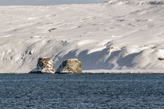 Rocks stand in the sea against the backdrop of snow-covered coast Stock Image