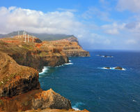 Rocks steeply in the Atlantic Ocean. Over a cliff on the ocean breeze are the windmills. Eastern tip of the island of Madeira. Rocks steeply in the blue waters Royalty Free Stock Image