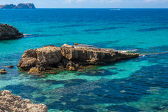 Rocks sticking out of the sea at the coast of Mallorca Royalty Free Stock Images