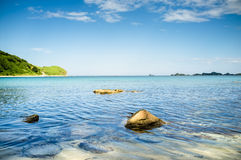Rocks sticking out of the water on the shore of the solar ocean beach Royalty Free Stock Images