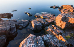 Rocks of stony coast in calm water of lake Stock Images