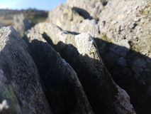 Rocks and the Sun. A landscape captured from midway up a wall giving way to a glimpse of the sun Stock Images
