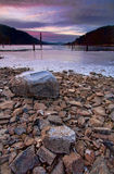 Rocks at sunset by the lake. Royalty Free Stock Image