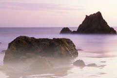 Rocks in Surf at California Beach. Rocks sit in the surf at sunset at a California Beach in Malibu Royalty Free Stock Photos