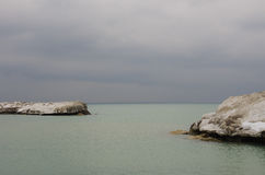 Rocks täckte i is och snö nära en tom sandig strand Arkivfoton