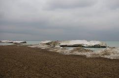 Rocks täckte i is och snö nära en tom sandig strand Royaltyfri Fotografi