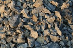 Rocks texture from a stone quarry at sunset Royalty Free Stock Images