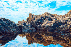 Rocks and their reflection in the sea Stock Photos