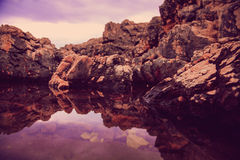 Rocks and their reflection in the sea at sunrise Stock Photos