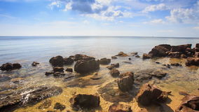 Rocks under above Transparent Shallow Water by Beach. Camera moves along rocks under and above transparent shallow sea water near beach against azure sea sky and stock video footage
