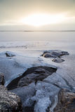 Rocks under cracked ice at a frozen lake Royalty Free Stock Image