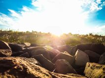 Sunlight hits the lens of the camera while observing some rocks on the riverbank. The rocks are undoubtedly beautiful, but when the sun illuminates their Royalty Free Stock Image