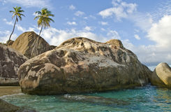 Rocks on Virgin Gorda Island. A view of volcanic rocks and palm trees along the shoreline at the baths, a popular swimming and snorkeling area on the island of stock images
