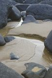 Rocks and Washout. Close up of rocks and boulders with a wash-out stream through the sand royalty free stock photo