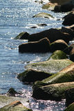 Rocks and water. A view of the rocks and water with the sun glistening down royalty free stock photos