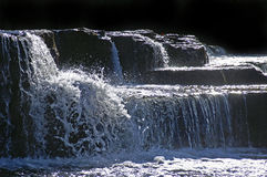 Rocks and water. White water cascading over black rocks in river Stock Image