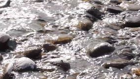 Rocks with water flowing around. water waves under the stone, water surface stock video footage