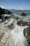 Rocks on water's edge. A closeup of some rocks on the water's edge on a peaceful beach in Hawaii, USA Stock Image
