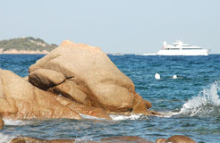 Rocks, waves, a boat. Rocks and waves with a white boat on background Royalty Free Stock Images