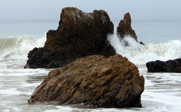 Rocks and Waves Collide Off the Coast of Malibu. A rock formation off the coast of California`s El Matador Beach is about to bear the brunt of impact from waves Stock Image